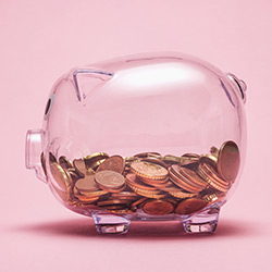Clear piggy savings bank with coins